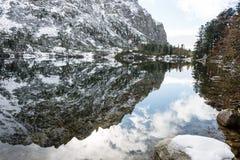 Les réflexions dans le lac calme arrosent avec la neige et les montagnes Photos libres de droits