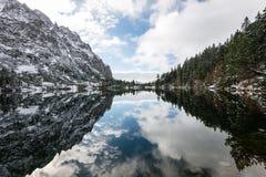 Les réflexions dans le lac calme arrosent avec la neige et les montagnes Image stock