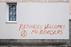 Les réfugiés font bon accueil au graffiti dedans sur le mur à Varsovie photo stock