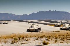 Les réservoirs d'armée manoeuvrent dans le sable blanc de désert photographie stock libre de droits