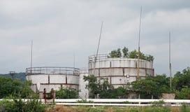 Les réservoirs de stockage de pétrole gris en métal sur le lac marchent Photo stock