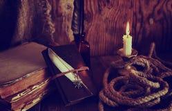 Les rétros objets font varier le pas et le livre de leaher avec la lumière de bougie Photographie stock