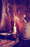 Les rétros objets font varier le pas et le livre de leaher avec la lumière de bougie Photos libres de droits