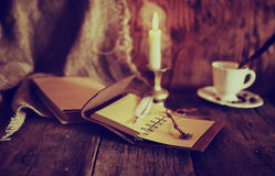 Les rétros objets font varier le pas et le livre de leaher avec la lumière de bougie Photos stock