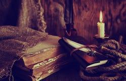 Les rétros objets font varier le pas et le livre de leaher avec la lumière de bougie Photo stock