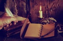 Les rétros objets font varier le pas et le livre de leaher avec la lumière de bougie Image libre de droits