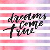 Les rêves viennent lettrage vrai sur des rayures d'aquarelle dans les couleurs violettes et roses Images stock