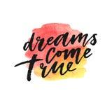 Les rêves viennent véritable lettrage tiré par la main sur l'éclaboussure d'aquarelle dans des couleurs rouges et jaunes Photographie stock libre de droits
