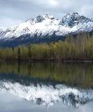 Les r?flexions de l'Alaska dans le printemps avec la neige ont couvert des montagnes comme contexte image stock