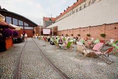 Les rails de tram sur le territoire du vieux dépôt sont maintenant devenus en café extérieur moderne et populaire Photographie stock