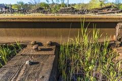 Les rails en acier se sont boulonnés vers le bas aux traverses en bois Photo libre de droits