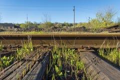 Les rails en acier se sont boulonnés vers le bas aux traverses en bois Photos libres de droits
