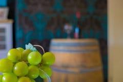les raisins devant une bouteille de vin sur un chêne barrel Images stock