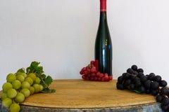 Les raisins et une bouteille de vin sur un chêne barrel Images stock