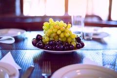 Les raisins mûrs s'étendent sur des plats table servie gobelets en verre, couteau, fourchette, serviettes photos stock