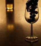 Les raisins silhouettent dans un verre à vin Photos libres de droits