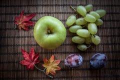 Les raisins vert pomme de feuilles d'automne verdissent la prune et la biscotte Image stock