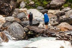 Les randonneurs croisent le pont en bois en montagnes de l'Himalaya sur M image stock