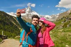 Les randonneurs d'un couple trimardant avec des sacs à dos marchent le long d'un beau secteur de montagne Photographie stock