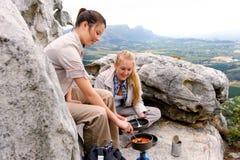 Les randonneurs de montagne font cuire la nourriture images libres de droits