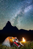Les randonneurs de paires s'asseyant près de la tente et du feu de camp rougeoyants, regardant au brille le ciel étoilé dans le c Images libres de droits