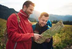 Les randonneurs de sourire lisant une traînée tracent dans la région sauvage photos libres de droits