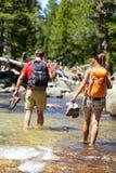 Les randonneurs groupent la rivière aux pieds nus de marche de croisement Image libre de droits