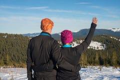 Les randonneurs heureux de couples étreignant pendant l'hiver voyagent dans le Carpath Photographie stock