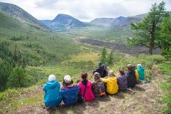 Les randonneurs ont un repos sur un flanc de coteau avec la belle vue aux montagnes, les gens détendent sur l'activité d'été Photo libre de droits