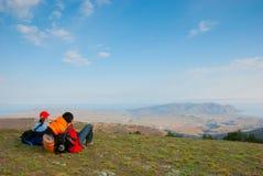 Les randonneurs s'asseyent sur la pente Photographie stock libre de droits