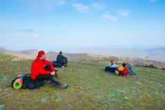 Les randonneurs s'asseyent sur la pente Image stock