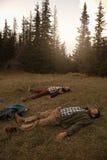Les randonneurs se trouvant sur l'herbe après une longue région sauvage trek Images stock