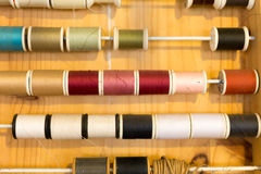 Les rangées de couleur de couture filète le cadre sur la table en bois Photo libre de droits
