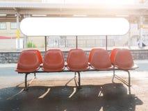 Les rangées de l'les sièges en plastique oranges vides avec le signe blanc embarquent dans r images stock