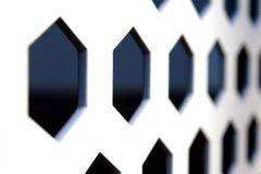 Les rangées des trous formés hexagonaux sur un métal blanc embarquent Photos stock