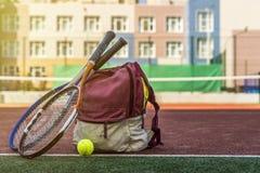 Les raquettes de tennis avec une boule près du sport mettent en sac avec l'équipement sur la cour le jour d'été photographie stock