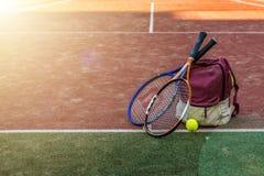 Les raquettes de tennis avec une boule près du sport mettent en sac avec l'équipement sur la cour le jour d'été image libre de droits