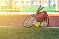 Les raquettes de tennis avec une boule près du sport mettent en sac avec l'équipement sur la cour le jour d'été photographie stock libre de droits