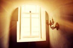 Les rayons du ` s du soleil pénètrent par la fenêtre d'un vieux bâtiment Images stock