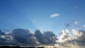 Les rayons du soleil brillent au-dessus des nuages foncés sur le fond de ciel bleu Photo stock