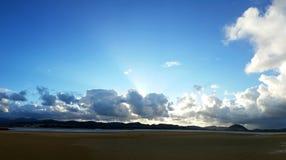 Les rayons du soleil brillent au-dessus des nuages foncés sur le fond de ciel bleu au-dessus de la rivière Photographie stock