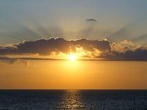 Les rayons du soleil de configuration traverse les nuages Image stock