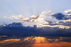 Les rayons du soleil font leur voie par les nuages, le ciel Image libre de droits