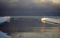 Les rayons du soleil illuminent la fin de l'hiver marin de brise-lames photographie stock libre de droits
