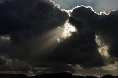 Les rayons lumineux du soleil brillent des nuages d'obscurité de cuvette Images stock