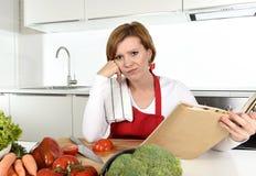 Les recettes de lecture ennuyées et frustrées de femme bouleversée de cuisinier réservent dans la cuisine à la maison dans l'effo photo stock