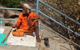Les recherches indoues indiennes d'homme supérieur aident ou aumône ou prient sur des escaliers de temple Photographie stock libre de droits