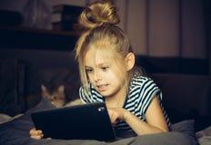 Les regards de fille ont ennuyé le comprimé Photographie stock libre de droits