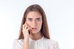 Les regards de jeune fille redressent et gardant sa main près du visage d'isolement sur le fond blanc Image libre de droits