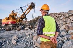 Les regards de travailleur sur l'excavatrice fonctionne à ciel ouvert Photo libre de droits
